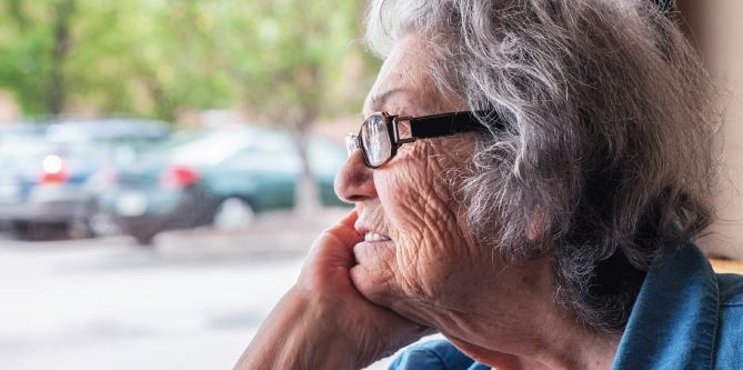 image of senior woman staring out of a window wistfully