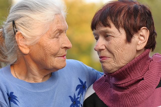 two senior women embracing and smiling