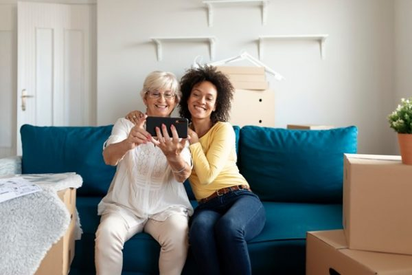 Mom and daughter taking a selfie on a camera phone while sitting on a blue couch in an emptied house surrounded by moving boxes