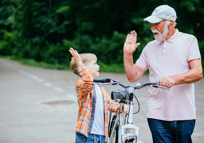 Boy and senior high five while walking their bike